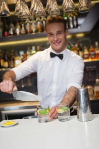 Happy bartender making a cocktail