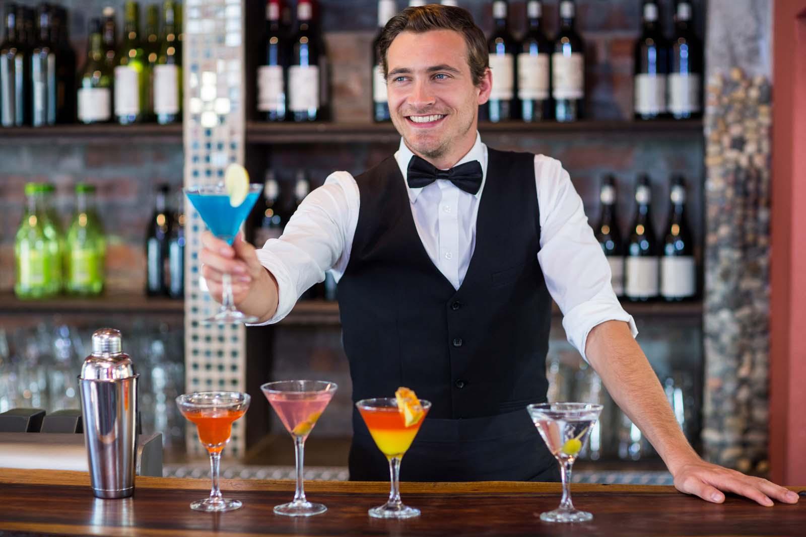 Bartender providing mixed drink to customer