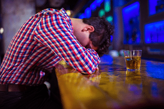 drunk man lying on counter of bar