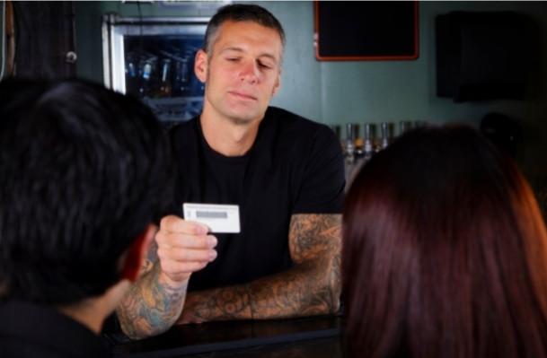 man checking an ID at the bar